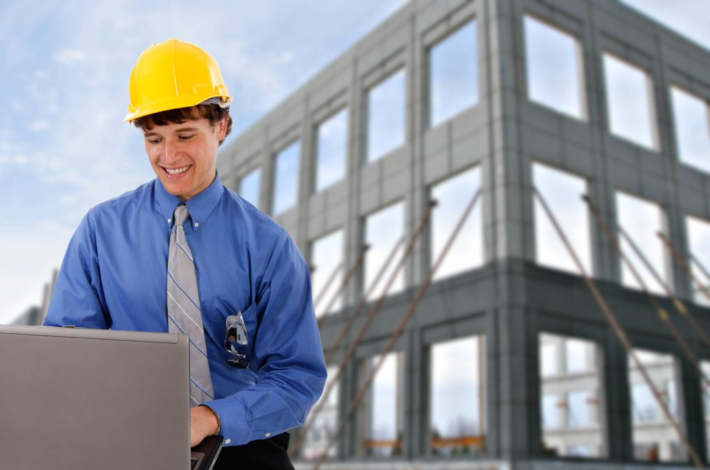 Commercial Inspector looking at his laptop smiling - Xcellence Inspection Services