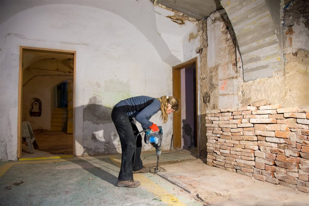 woman drilling the basement floor   Xcellence Inspection Services   Bathroom in the basement Chicago